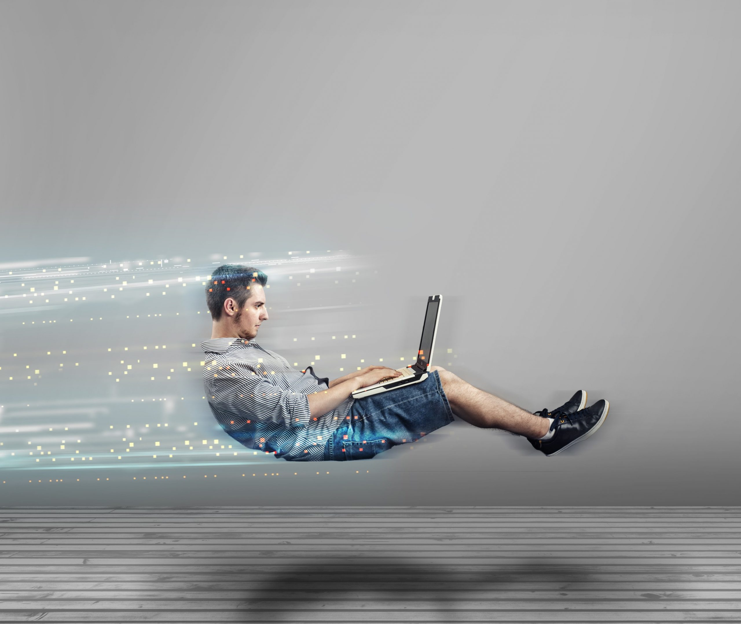 Fast levitating man in a white room using a laptop. High speed browsing.