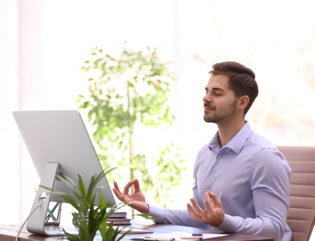 Young businessman meditating at workplace. Zen concept